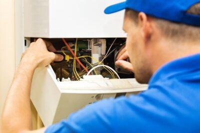 a man wearing blue polo shirt fixing boiler